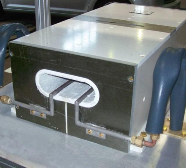 Eingehauste Induktionsspule mit gekühlten Gleitschienen